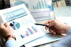 工作和分析在的商人财政图在膝上型计算机的图表外面 库存照片