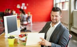 工作和回顾在一个文件夹的确信的男性设计师文件在红色创造性的办公室空间 库存照片