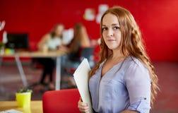 工作和回顾在一个文件夹里面的确信的女性设计师文件在红色创造性的办公室空间 免版税库存图片