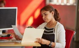 工作和回顾在一个文件夹里面的确信的女性设计师文件在红色创造性的办公室空间 库存照片