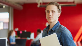 工作和回顾在一个文件夹里面的确信的男性设计师文件在红色创造性的办公室空间 免版税库存照片