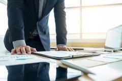 工作和指向图表文件财务proj的商人 图库摄影
