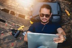 工作和检查在膝上型计算机的亚裔人照片在室外自然和他是放松,享用在旅行 免版税库存图片