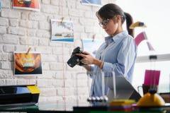 工作和检查数字照相机设置的摄影师在办公室 库存照片