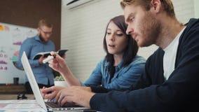 工作和沟通在办公桌的小组年轻商人看便携式计算机 股票录像