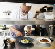 工作和烹调在厨房里的厨师 免版税库存照片