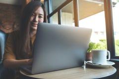 工作和键入在咖啡馆的膝上型计算机键盘的一名美丽的亚裔妇女 免版税库存图片