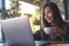 工作和键入在膝上型计算机键盘的一个美丽的亚裔女商人的特写镜头图象,当喝咖啡时 图库摄影
