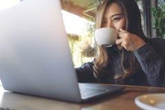 工作和键入在膝上型计算机键盘的一个美丽的亚裔女商人的特写镜头图象,当喝咖啡时 免版税库存照片