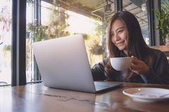 工作和键入在膝上型计算机键盘的一个美丽的亚裔女商人的特写镜头图象,当喝咖啡时 库存图片