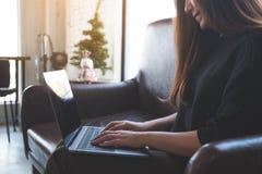 工作和键入在膝上型计算机键盘的一名亚裔妇女,当坐沙发时 免版税图库摄影