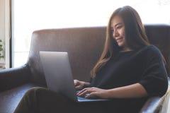 工作和键入在膝上型计算机键盘的一名亚裔妇女,当坐沙发时 库存照片