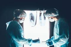 工作和集中在手术台上的两位外科医生 免版税库存照片