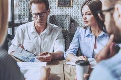 工作四个年轻的商人,当坐在咖啡馆时 免版税库存图片