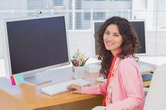 工作在一个创造性的办公室和微笑对照相机的妇女 图库摄影
