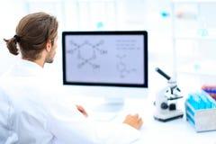工作在一个医学实验室的年轻人使用计算机 免版税库存图片