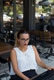 工作在一个室外咖啡馆的女商人 图库摄影