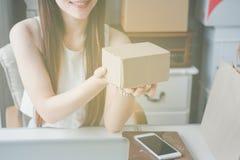 工作在一个家庭办公室的年轻亚裔妇女企业家 免版税图库摄影
