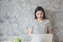 工作在一个家庭办公室的年轻亚裔妇女企业家 免版税库存照片