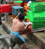 工作在一个批发鱼市上的人们 图库摄影