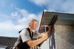 工作在一个新的屋顶窗的盖屋顶的人 免版税库存照片