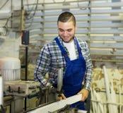 工作在一个机器的工作者在PVC商店 免版税库存照片