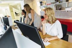 工作在一个现代办公室的美丽的妇女 图库摄影