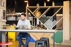 工作在一个现代咖啡馆的成功的年轻商人 免版税库存照片
