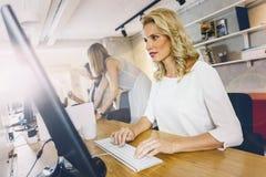 工作在一个现代办公室的美丽的妇女 免版税图库摄影