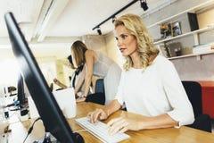 工作在一个现代办公室的美丽的妇女 库存图片