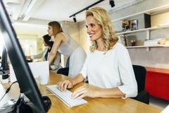 工作在一个现代办公室的美丽的妇女 库存照片