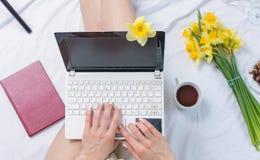 工作在一个笔记本的妇女在床上 免版税图库摄影