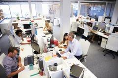 工作在一个繁忙的办公室的人们 免版税库存图片