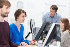 工作在一个繁忙的办公室的能干女实业家 免版税库存图片