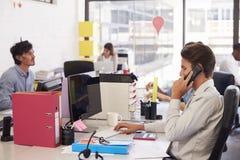 工作在一个繁忙的开放学制办事处的年轻企业队 免版税图库摄影