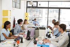 工作在一个繁忙的开放学制办事处的年轻企业队 库存图片