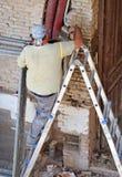 工作在一个老房子的修复的建筑工人 库存图片