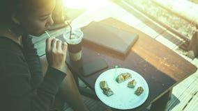 工作在一个自然公园的妇女使用笔记本 在咖啡馆 免版税库存图片