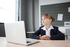工作在一台膝上型计算机后的一名小女实业家在桌面上的一个办公室 库存照片