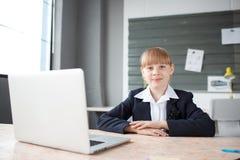 工作在一台膝上型计算机后的一名小女实业家在桌面上的一个办公室 免版税图库摄影