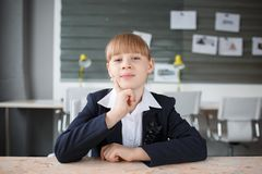 工作在一台膝上型计算机后的一名小女实业家在桌面上的一个办公室 免版税库存照片