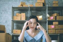 工作在一台膝上型计算机的年轻亚裔女孩在小中等企业中 免版税图库摄影