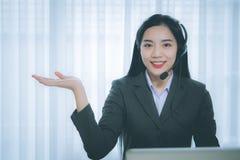 工作在一台膝上型计算机的年轻亚裔女孩在小中等企业中 库存照片