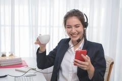 工作在一台膝上型计算机的年轻美丽的女孩在小中等企业中 免版税图库摄影