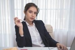 工作在一台膝上型计算机的年轻美丽的女孩在小中等企业中 免版税库存图片