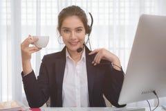工作在一台膝上型计算机的年轻美丽的女孩在小中等企业中 免版税库存照片