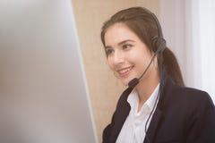 工作在一台膝上型计算机的年轻美丽的女孩在小中等企业中 库存图片