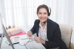 工作在一台膝上型计算机的年轻美丽的女孩在小中等企业中 库存照片