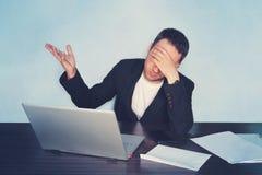 工作在一台计算机的商人在拿着他的头用他的手的办公室和闭上他的眼睛 企业probl的概念 免版税库存图片