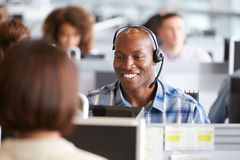 工作在一台计算机的非裔美国人的人在电话中心 免版税库存图片